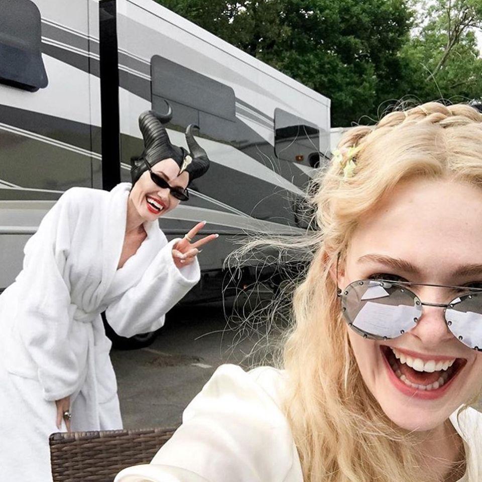 """Was für ein Schnappschuss! Elle Fanning postet dieses lustige Selfie von sich und """"Maleficent""""-Kollegin Angelina Jolie mit Maske und im Bademantel. Sieht so aus, als hätten die beiden richtig viel Spaß, und umso mehr freuen wir uns auf die Fortsetzung des Kinoerfolgs."""