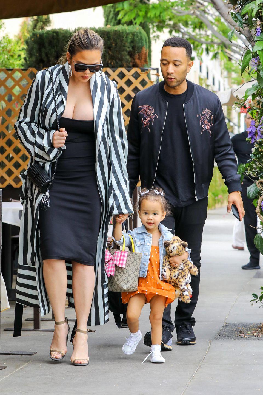 Dieser Look versteckt nichts: Nur elf Tage nach der Geburt ihres ersten Kindes zeigt sich Chrissy Teigen in einem schwarzen, engen Kleid beim Familien-Spaziergang. Über dem Kleid trägt sie einen schwarz-weiß-gestreiften Kimono-Mantel. Dem Model ist nicht anzusehen, dass sie erst vor wenigen Tagen ein Kind zur Welt gebracht hat.