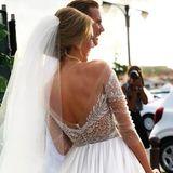 Ein tiefer Rückenausschnitt und die hochgesteckten Haare setzen den Rücken der Braut und ihre zierliche Silhouette perfekt in Szene. Der durchsichtige Stoff lässt tief blicken, aber nicht zu tief. Ein wunderbares Kleid!