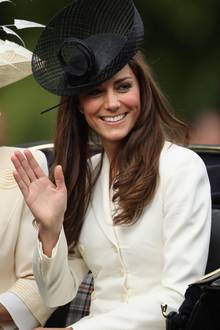 In einem zartgelben, doppelreihigen Blazerdress von Alexander McQueen setzt sie erneut auf das Modehaus, aus dem auch ihr legendäres Brautkleid stammte. Dazu kombiniert sie einen schwarzen, geflochtenen Hut mit aufstehender, breiter Schärpe. Ihr Haar trägt sie offen und in leichten Wellen.