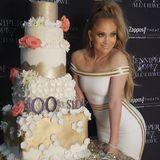 """Was für eine grandiose Torte! Jennifer Lopez feiert ihre 100. """"All i have""""-Show in Las Vegas mit einem mitRosen verzierten fünfstöckigen Backwerk. Passend dazu. JLO's Off-Shoulder Kleid in Weiß mit Goldelementen."""
