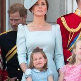 In einem blauen Kleid mit weißem Blumenmuster und Peter-Pan-Kragen zeigt sich Prinzessin Charlotte auf dem Balkon des Buckingham Palace – Ton in Ton mit Mama Herzogin Catherine. Besonders süß: Die rote Schleife im Haar der Dreijährigen.