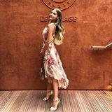 Das geblümte Kleid von Zimmermann begeistert mit kleinen Rüschen und dünnen Trägern. Dazu trägt sie helle Riemchen-Heels und eine rosé-farbene Valentino-Tasche. Ihre Haare trägt sie in leichten Locken - schöner könnte ein Sommer-Outfit kaum sein!