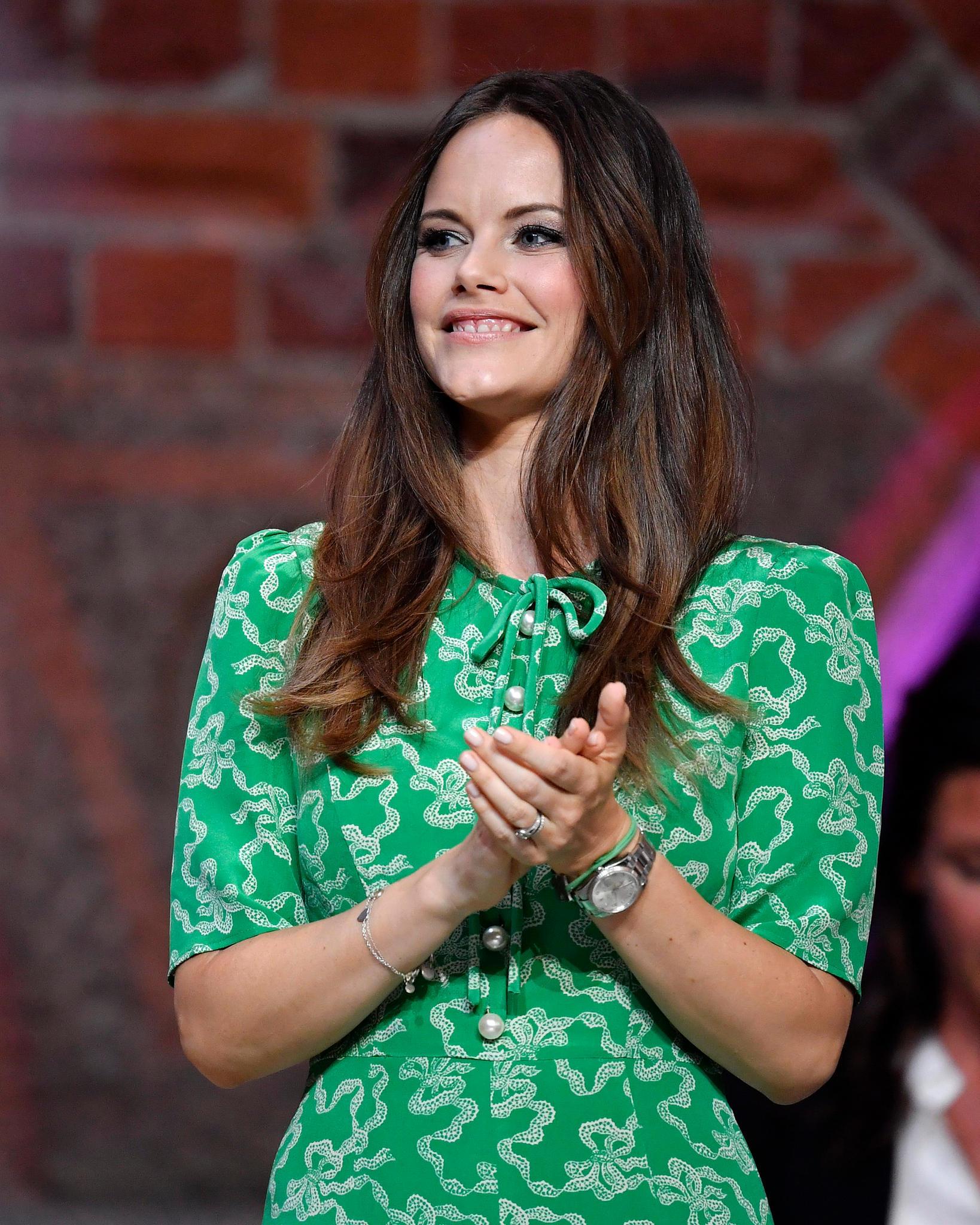 Die Knopfleiste des Kleides ist mit großen Perlen versehen, dezente Puffärmel verleihen dem Look einen mädchenhaften Touch. Prinzessin Sofia wählt zu dem Kleid in Grüntönen nudefarbene Accessoires ...
