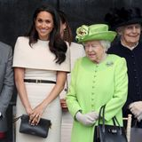 Ein Cape bedeckt Meghans Schultern, ihre Handtasche hat keineHenkel und das Kleid ist lang genug. Meghan bricht also mit keiner royalen Mode-Regel.