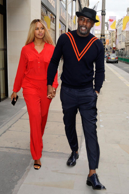 Idris Elba und Sabrina Dhowre sind in ihren dunkelblauen und roten Outfits echte Dresscode-Brecher. Stylisch sehen die beidentrotzdem aus.
