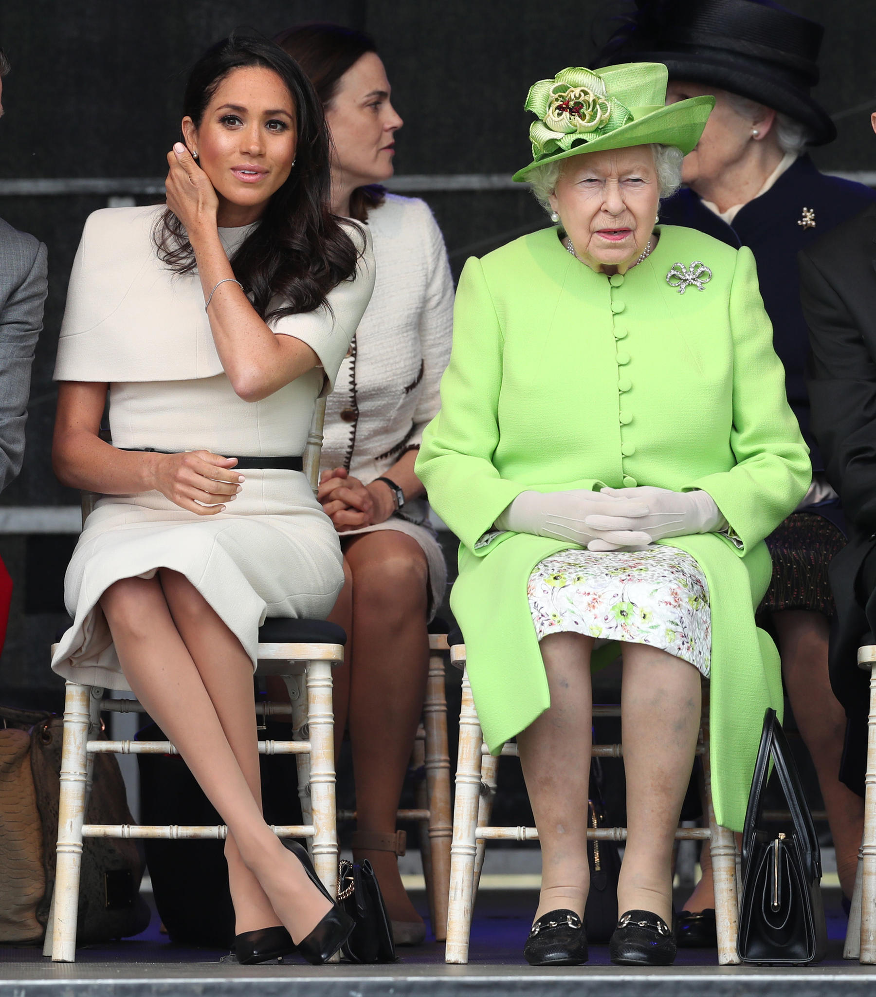 Ist das ein Zeichen? Die Queen stellt neben Herzogin Meghan ihre Handtasche auf die linke Seite. Eigentlich wird nun das Personal in Alarmbereitschaft versetzt und soll die Königin aus der Situation retten.