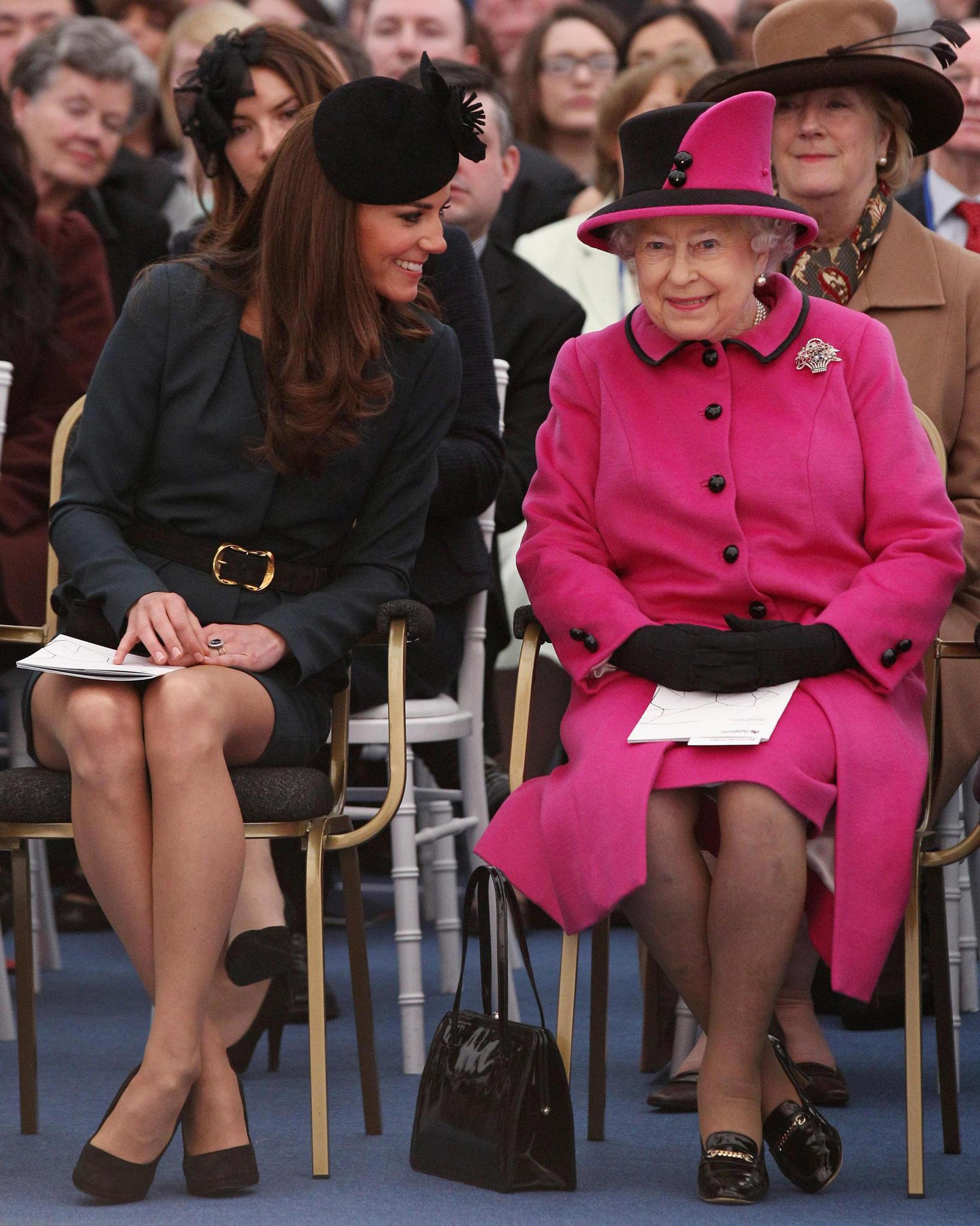 An der Seite von Herzogin Catherine scheint sich die Queen deutlich wohler zu fühlen. Die Tasche steht gut sichtbar auf der rechten Seite.