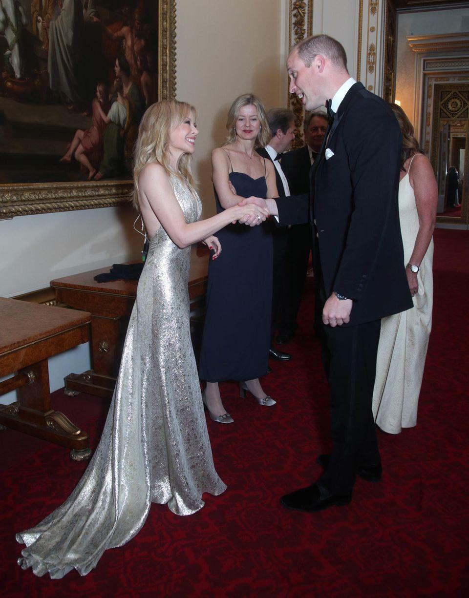 14. Juni 2018  Bei einem Benefiz- Dinner zugunsten von Krebsbehandlung in Krankenhäusern im Buckingham Palace ist auch der Popstar Kylie Minogue geladen. Freundlich begrüßt Prinz William den prominenten Gast. Der australische Popstar trägt ein zauberhaftes Metallic-Kleid.