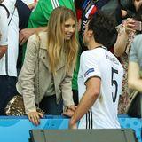 Bei der EM 2016 in Paris bekommt Mats Hummels Unterstützung von seiner Cathy, die eine relativ dezente Wildlederjacke trägt. Dafür gliztert ihre Umhängetasche umso doller.