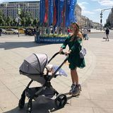 Angekommen in Moskau zeigt sich Cathy Hummels mit Ludwig im Kinderwagen gleich ganz sommerlich im dunkelgrünen Kleid und extrahohen geschnürten Bast-Wedges.