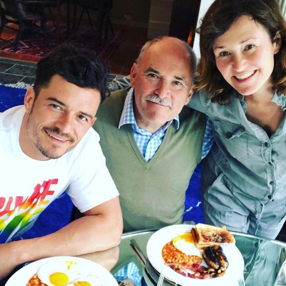 """""""Ein total englisches Frühstück mit einer total englischen Familie"""", schreibt Schauspieler Orlando Bloom zum Vatertag. Neben ihm und dem leckeren Essen sind auf dem Foto seine Eltern zu sehen: VaterColin Stone und MutterSonia Copeland."""