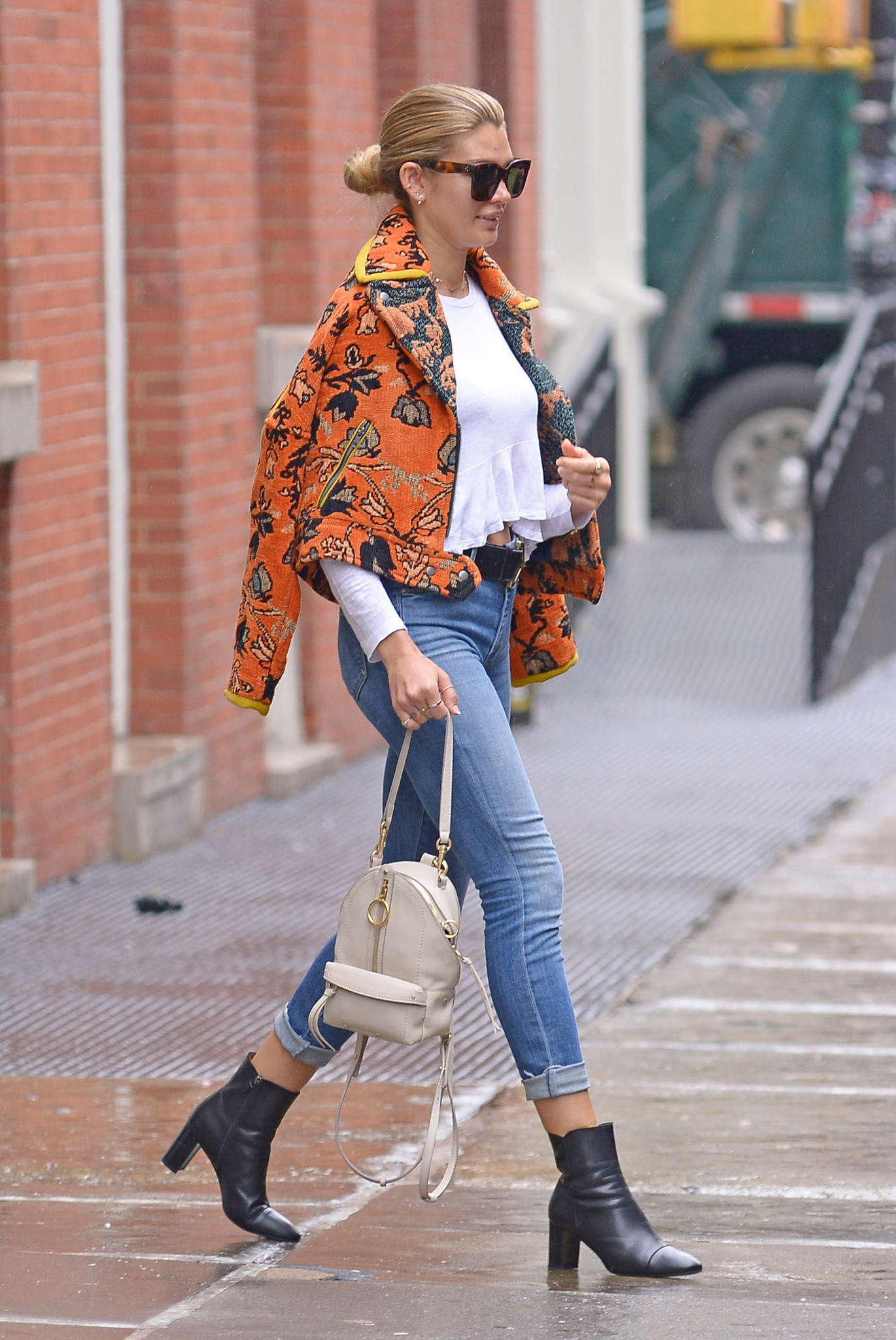 Model Shayna Taylor kombiniert eine orangene Statement-Jacke lässig mit einem weißen Basic-Shirt und Jeans