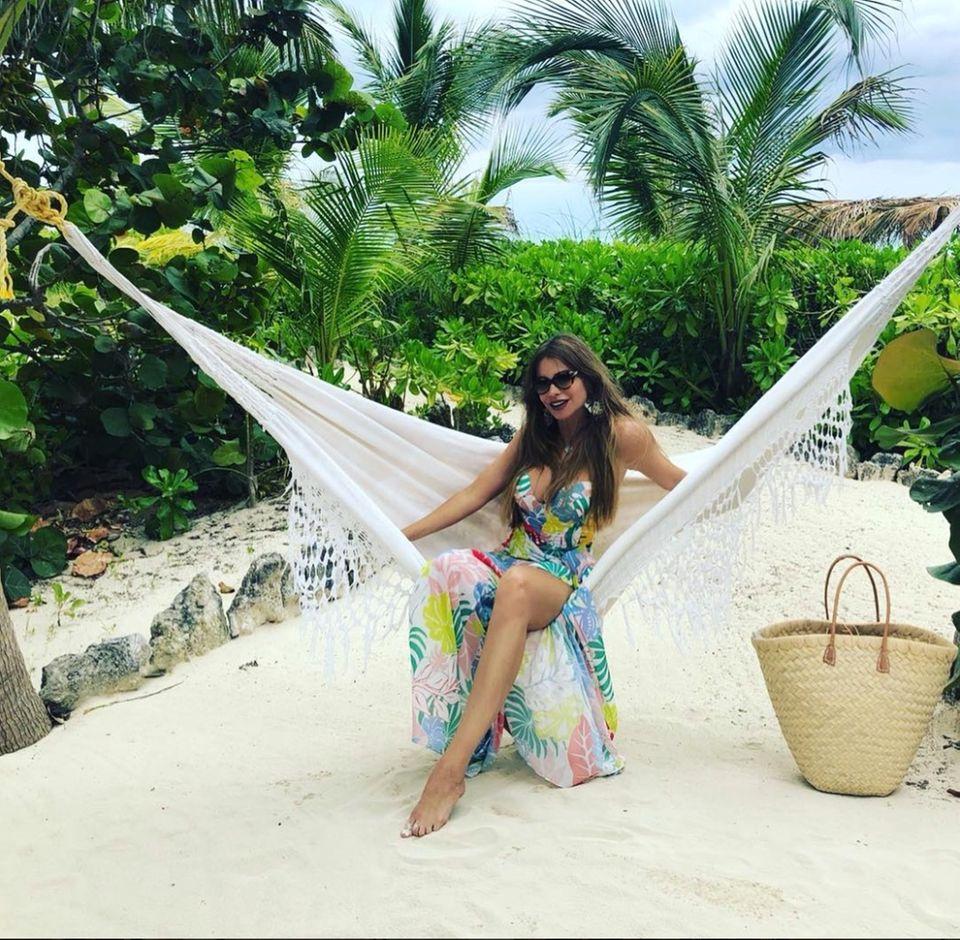 Sofia Vergara zeigt sich in lässiger Pose in einer Hängematte am Strand. In einem bunt gemusterten Wickelkleid und mit XL-Sonnenbrille versprüht sie echte Glamour-Vibes.