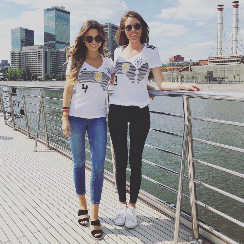 Christina und Anika, die Partnerinnen von Matthias Ginter und Jonas Hector zeigen in Russland, wie lässig ein Stadion-Look sein kann: Beide kombinieren zu ihren Trikots skinny Jeans und Sonnenbrille. Während Christina sich für schwarze Mules entscheidet, trägt Anika weiße Sneakers.