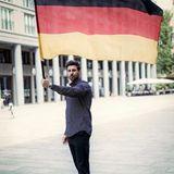 Ex-Bachelor Leonard Freier schwenkt die Farben Schwarz, Rot und Gold.