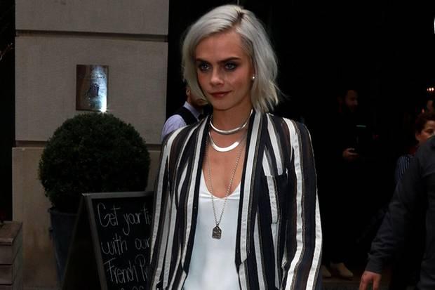 Model Cara Delevingne rockt ihr weißes Outfit mit einem gestreiften Blazer auf.