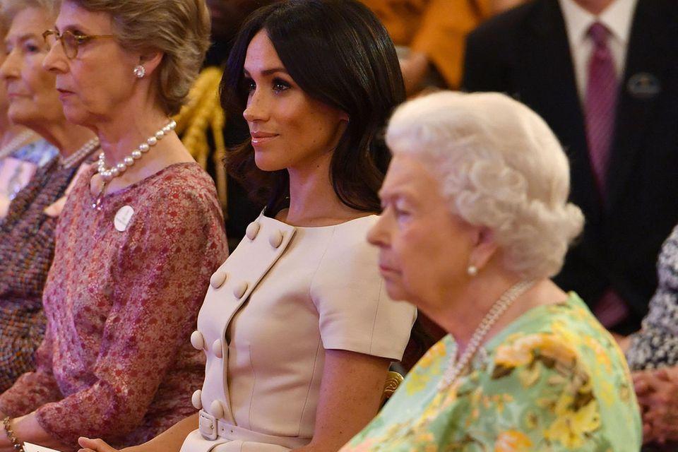 Herzogin Meghan macht es genauso wie die Queen: Sie sitzt kerzengerade, die Hände liegen gefaltet im Schoß.