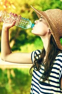 Eine Frau trinkt Wasser aus der Flasche (Symbolbild).