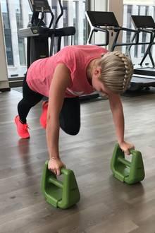 Um ihre Mountain Climbers zu intensivieren, stützt sich Valentina Pahde zusätzlich auf Gewichten ab. Jetzt ist volle Körperspannung gefragt.