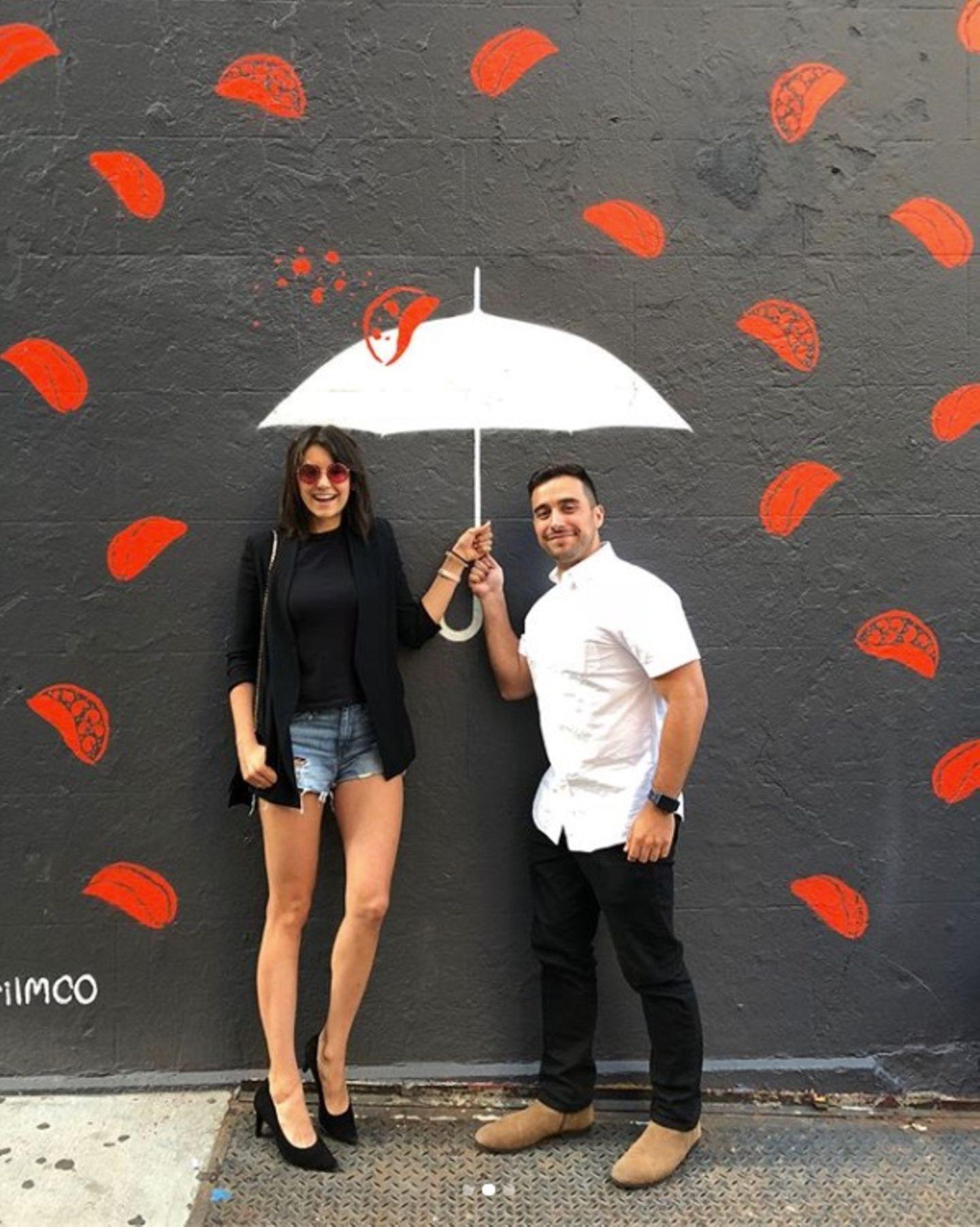 """""""Es regnet Tacos"""", postet Nina Dobrev scherzend. Erst bei genauerem Hinsehen wird klar, dass der Schirm und die Tacos auf die Wand imHintergrund gemalt sind."""