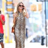 """Eisschlürfend spaziert Heidi Klum durch New York. Oder hüpft sie eher? Die Momentaufnahme erweckt den Eindruck, die """"GNTM""""-Jurorin habe nur ein Bein."""