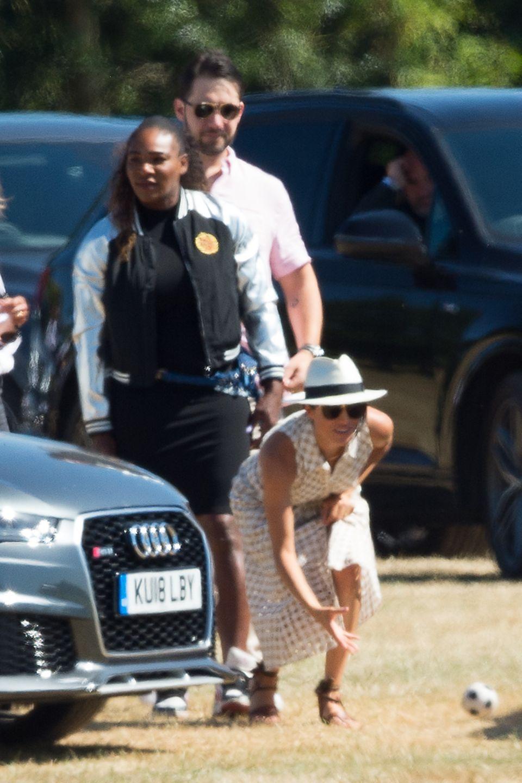Serena Williams steht hinter ihrer Freundin, Herzogin Meghan, die mit einem Kind Ball spielt.