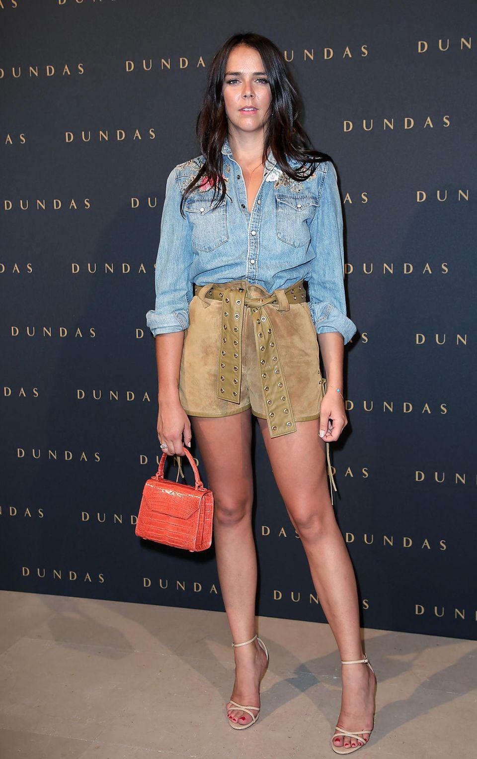 Auch Pauline Ducruet wechselt erneut das Outfit: Für die Dundas-Show trägt sie eine helle Wildledershorts und ein Jeans-Hemd. Dazu kombiniert sie eine kleine Tasche in Orange und helle Riemchen-Heels.