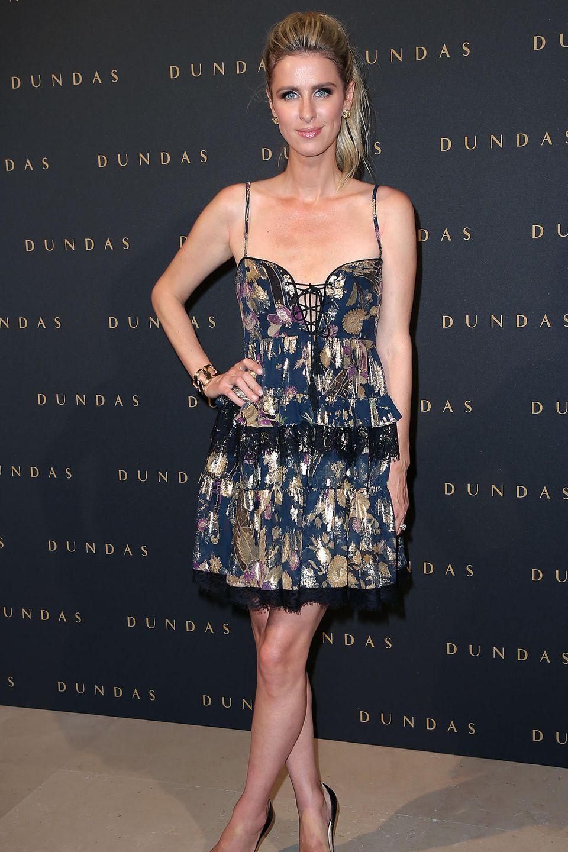 Ein dritter Look an nur einem Tag: Für die Show von Dundas wählt Nicky Hilton ein kurzes Kleid mit Korsagen-Schnürung, Spitze und Muster. Dazu trägt sie dunkles Augen-Make-up und nur die Frisur ist die gleiche.