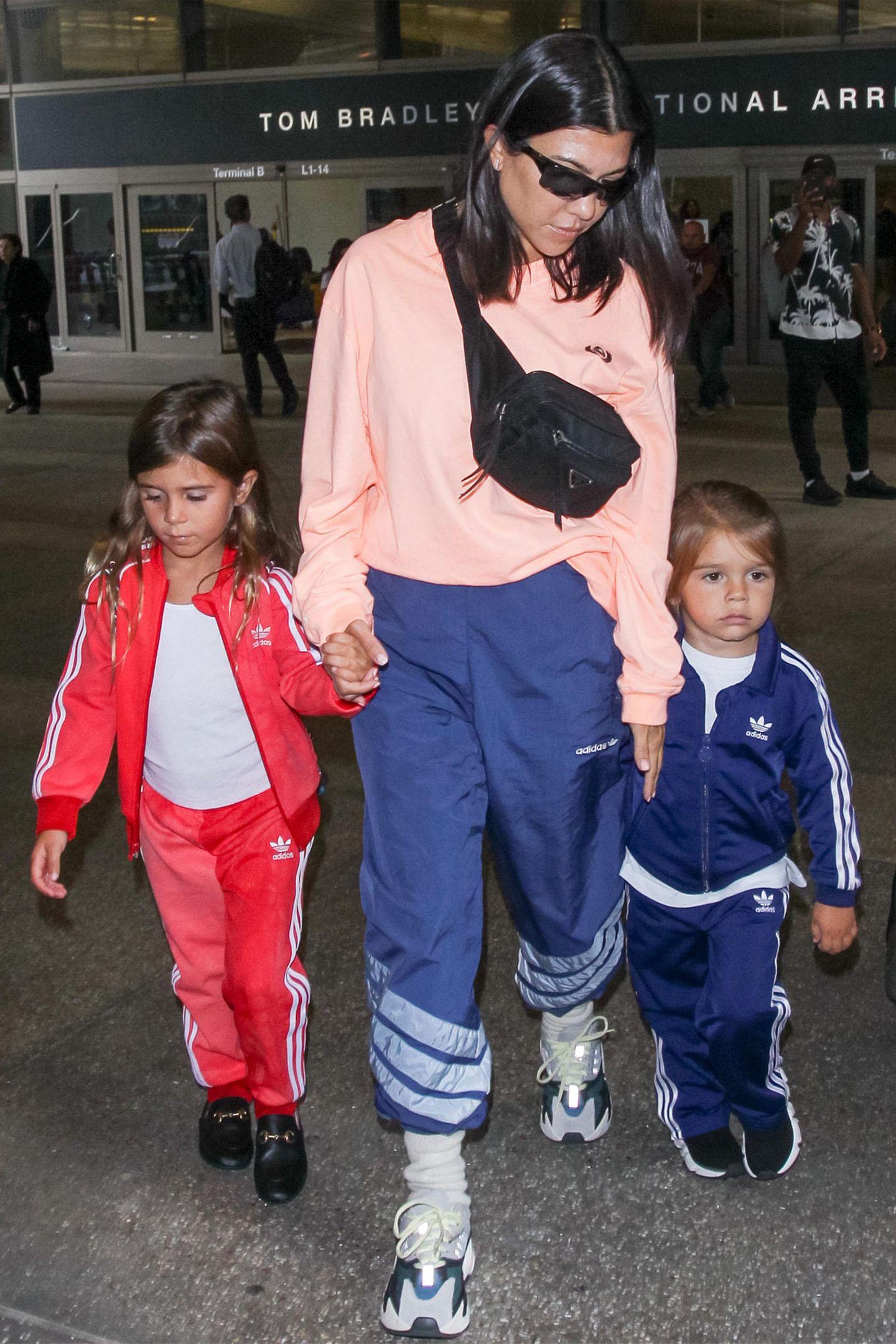 Im Flodder-Look am Flughafen: Kourtney Kardashian ist mit ihren Kids Penelope und Reign ganz gemütlich im Trainingsanzug-Partnerlook am LAX unterwegs. Wohl das bequemsteOutfit für lange Flugreisen, besonders mit Kindern.