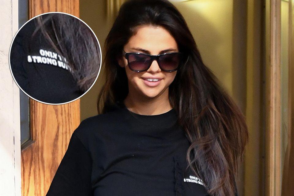 """Auf Selena Gomez Shirt steht klein und dennoch kenntlich """"Only the Strong Survive"""""""