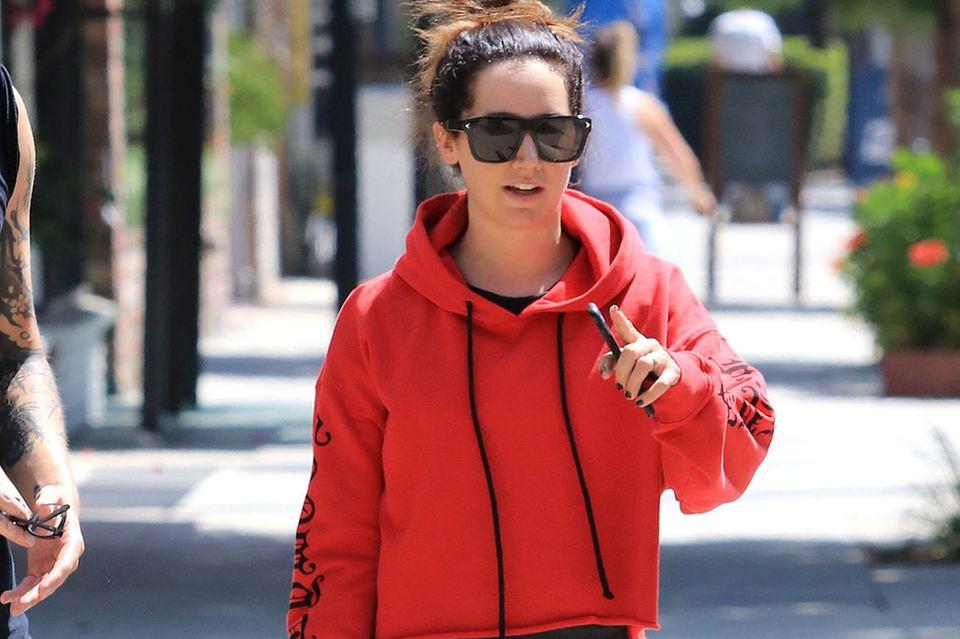 Ashley Tisdale mag warme Töne. Ihr After-Workout-Pullover ist rot und hat an den Ärmeln schwarze Tribals.
