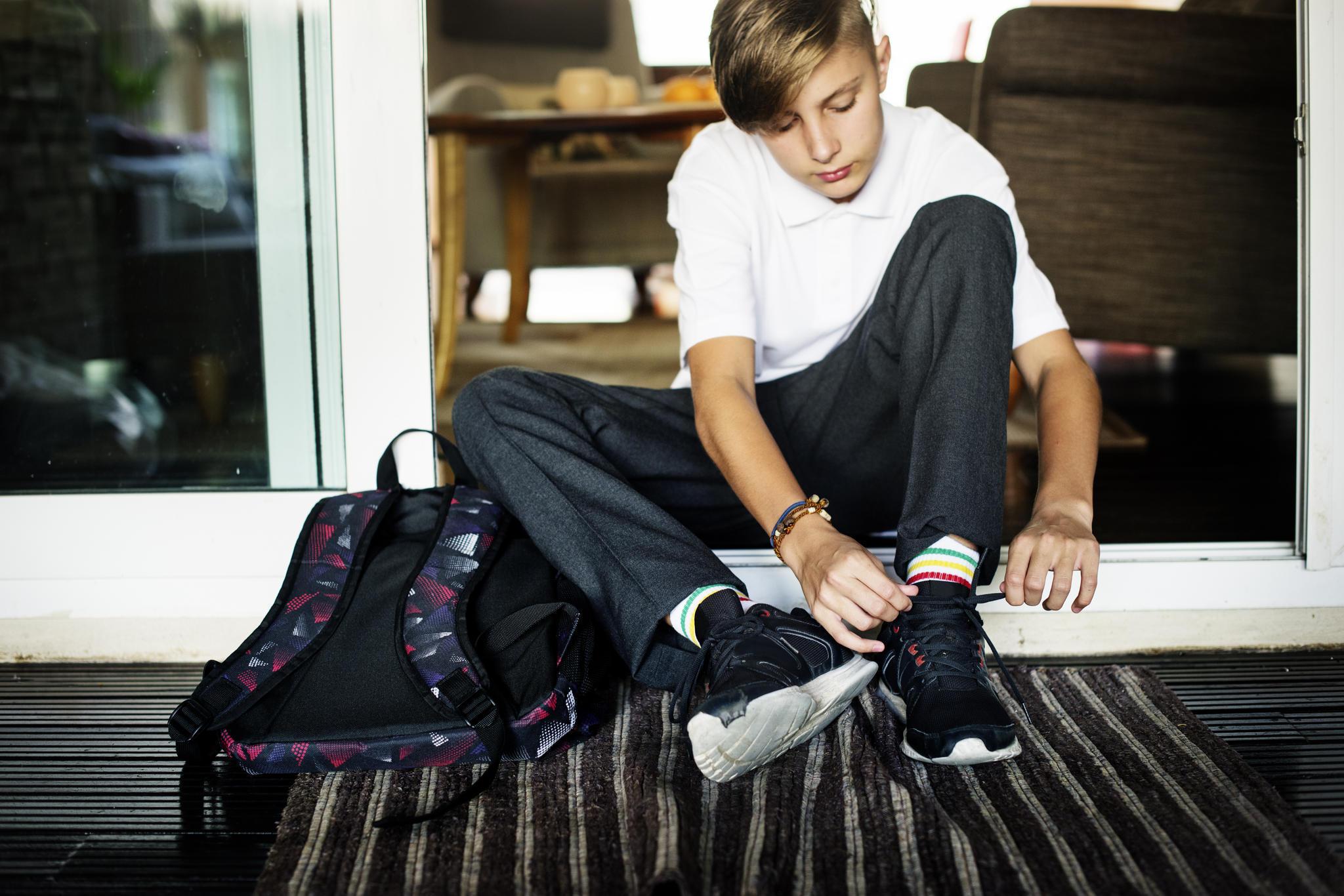 Junge bindet Turnschuhe (Symbolbild)