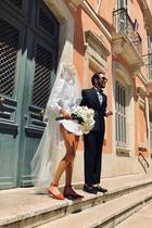 Stylistin Lolita Jacobs heiratet in einem weißen Männerhemd, das sie an der Taille knotet. Dazu trägt sie orangefarbene Ballerinas und einen langen weißen Schleier. Ein denkbar ungewöhnliches Brautkleid, das ihre langen Beine dennoch in Szene setzt.