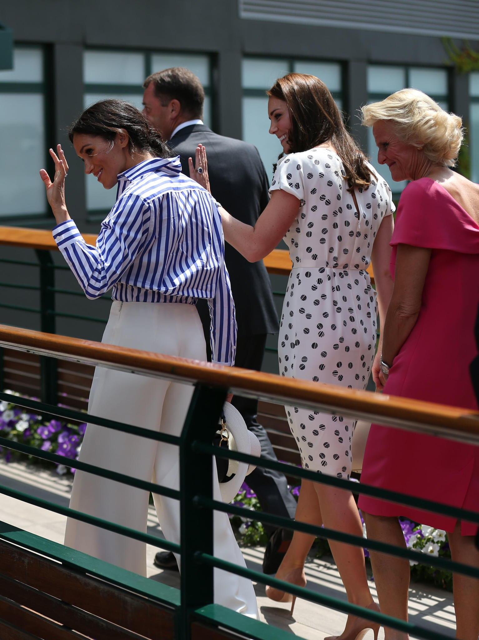 Winkend begrüßt das royale Duo die Fans in Wimbledon.