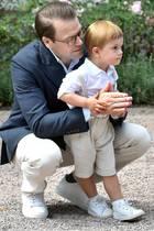 Der kleine Oscar erscheint im Partnerlook mit Papa Daniel: Beide tragen helle Hosen und Sneaker. Oscars Latzhose wird mit niedlichen Hosenträgern am Platz gehalten.