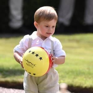 Der kleine Prinz Oscar spielt mit einem großen Ball.