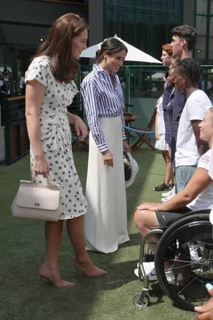 In einer weißen Marlenehose und einer blau-weiß-gestreiften Bluse von Ralph Lauren erscheint Herzogin Meghan an der Seite ihrer Schwägerin. Gemeinsam begrüßen sie vor dem Spiel die Balljungen und -Mädchen.