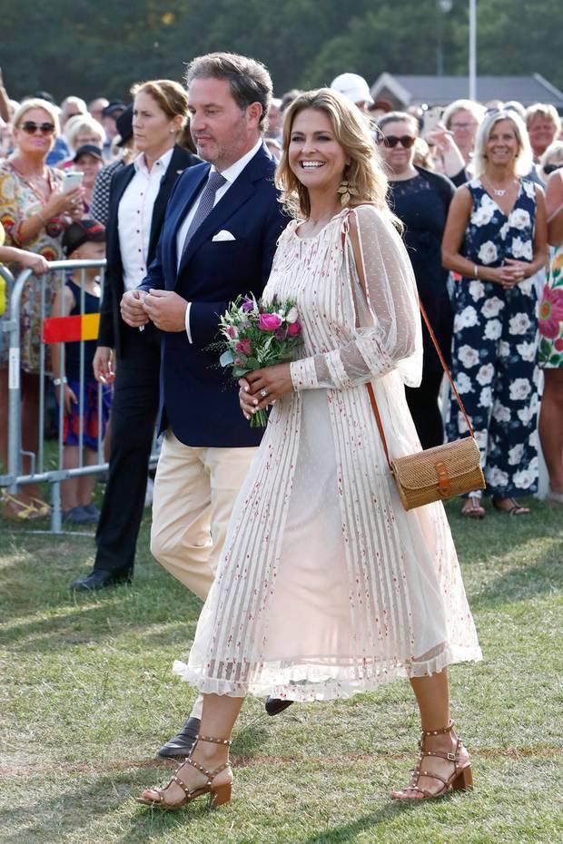Mit einem strahlenden Lächeln im Gesicht und ihrem Ehemann am Arm erscheint Prinzessin Madeleine zu den Feierlichkeiten anlässlich des 41. Geburtstags von Prinzessin Victoria. Sie trägt ein leicht durchsichtiges Kleid mit Rüschen und kleinem Blumenmuster.