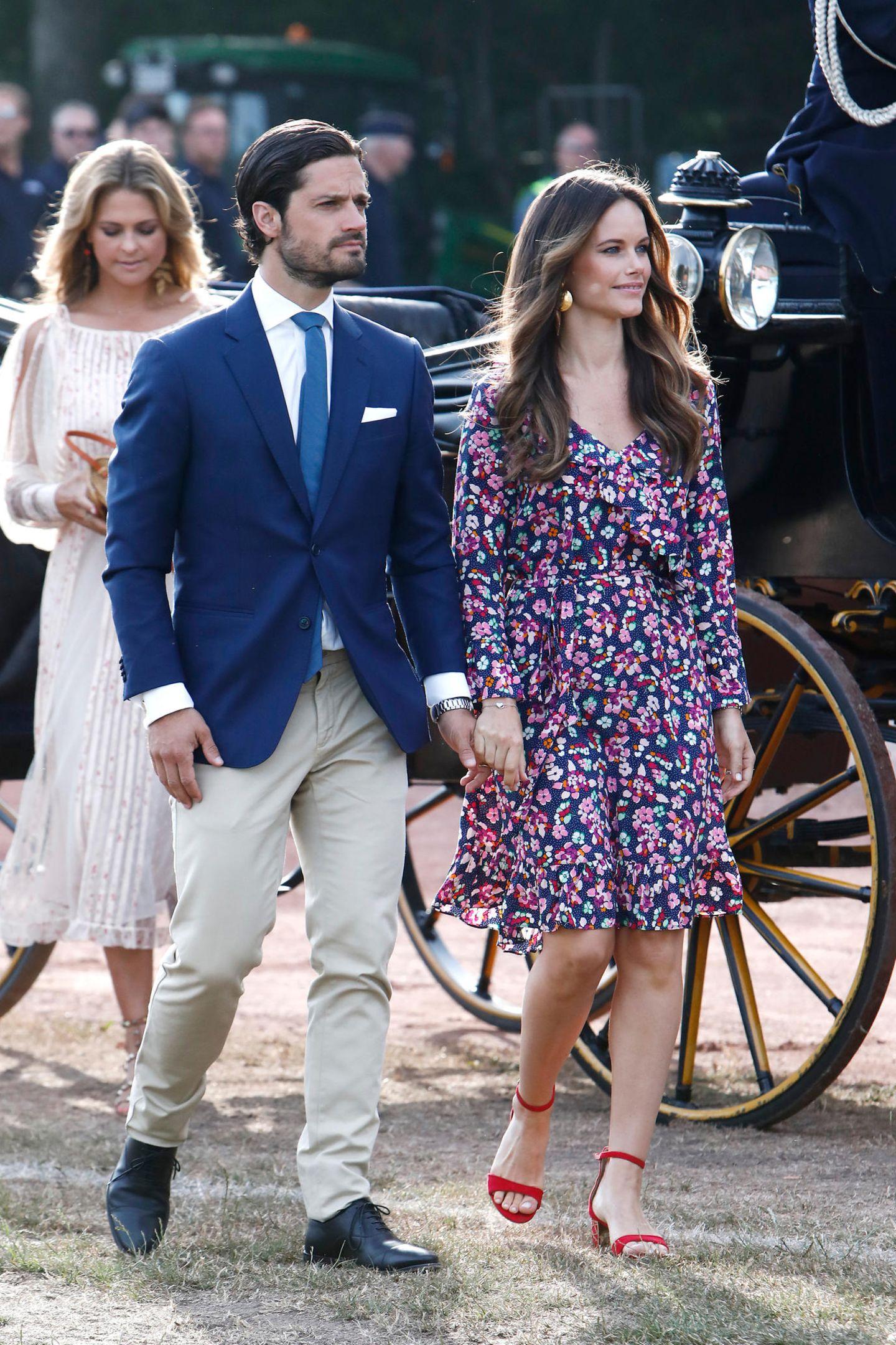 """Zu den Feierlichkeiten am Victoriatag, dem Geburtstag von Carl Philips älterer Schwester Victoria, erscheint Prinzessin Sofia in einem knielangen Kleid mit buntem Blumenmuster und Rüschen. Für knapp 60 Euro ist das bei """"& other stories"""" zu kaufen. Sie wagt einen farblichen Kontrast und kombiniert rote Riemchen-Heels dazu. Ob sie sich das irgendwo abgeschaut hat?"""