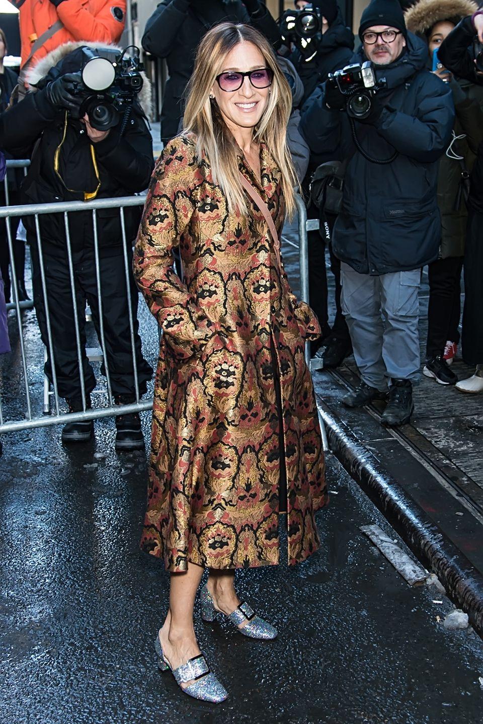 Dieses Outfit von Sarah Jessica Parker lieben wir ganz besonders. Die Schuhe mit Schnalle, der Mantel mit Print und diese getönte Sonnenbrille - wir wollen alles haben!