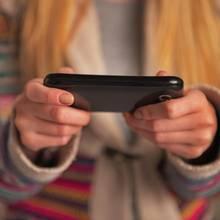 Frau wirft einen Blick auf das Handy ihres Mannes (Symbolbild)