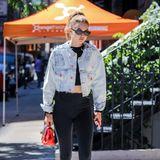 Mit einer Jeansjacke ohne Kragen und einer roten Mini-Bag setzt Gigi bei diesem sonst in schwarz gehaltenen Look gekonnt farbliche Akzente.