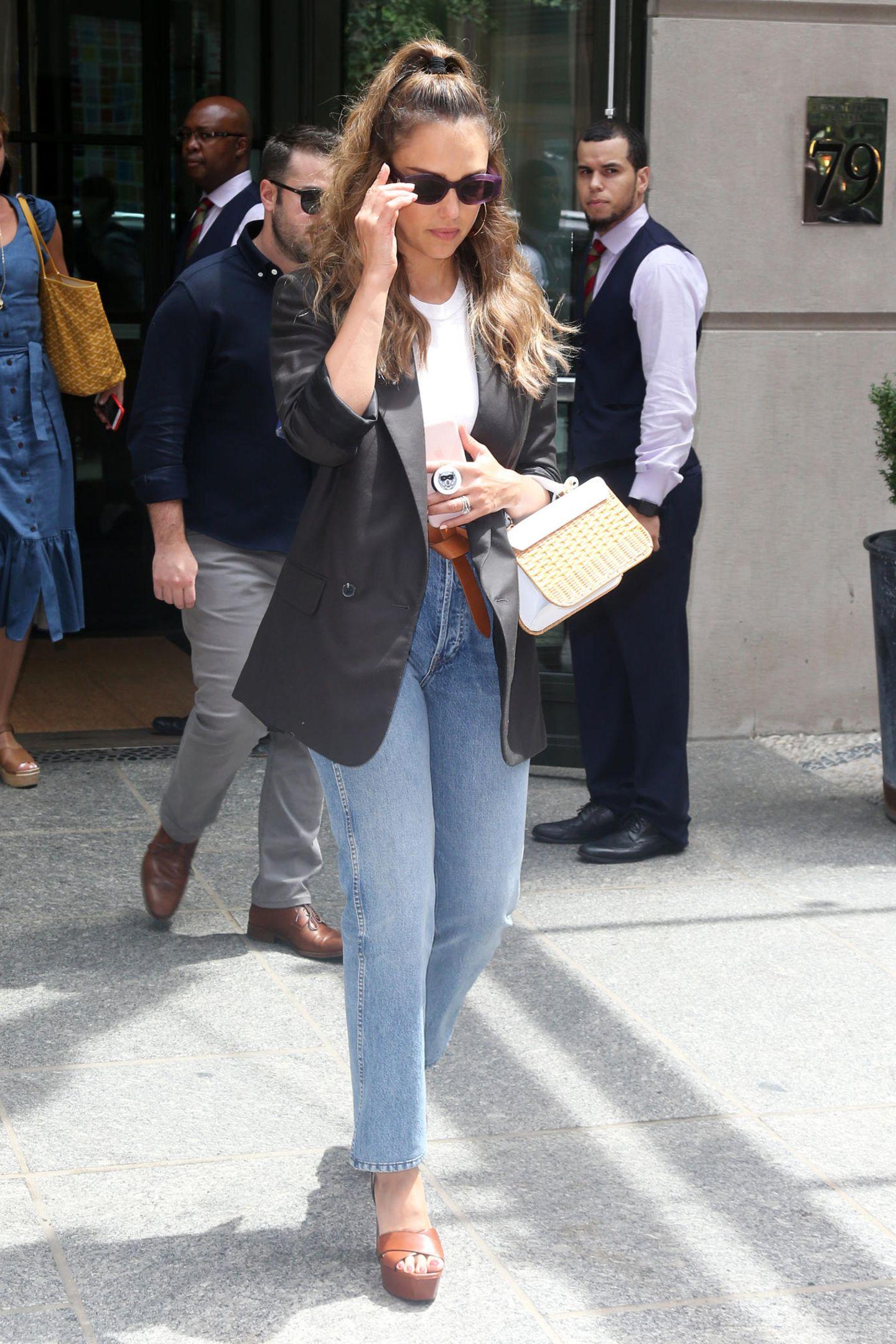 Perfekt gestylt verlässt Jessica Alba ihr Hotel in New York. Zur Jeans kombiniert sie ein schlichtes, weißes T-Shirt und einen schwarzen, doppelreihigen Blazer. Bei den Accessoires setzt sie auf Cognactöne und eine süße It-Bag. Nur wenige Stunden später zeigt sich die Schauspielerin dann in einem Casual-Look am Flughafen.
