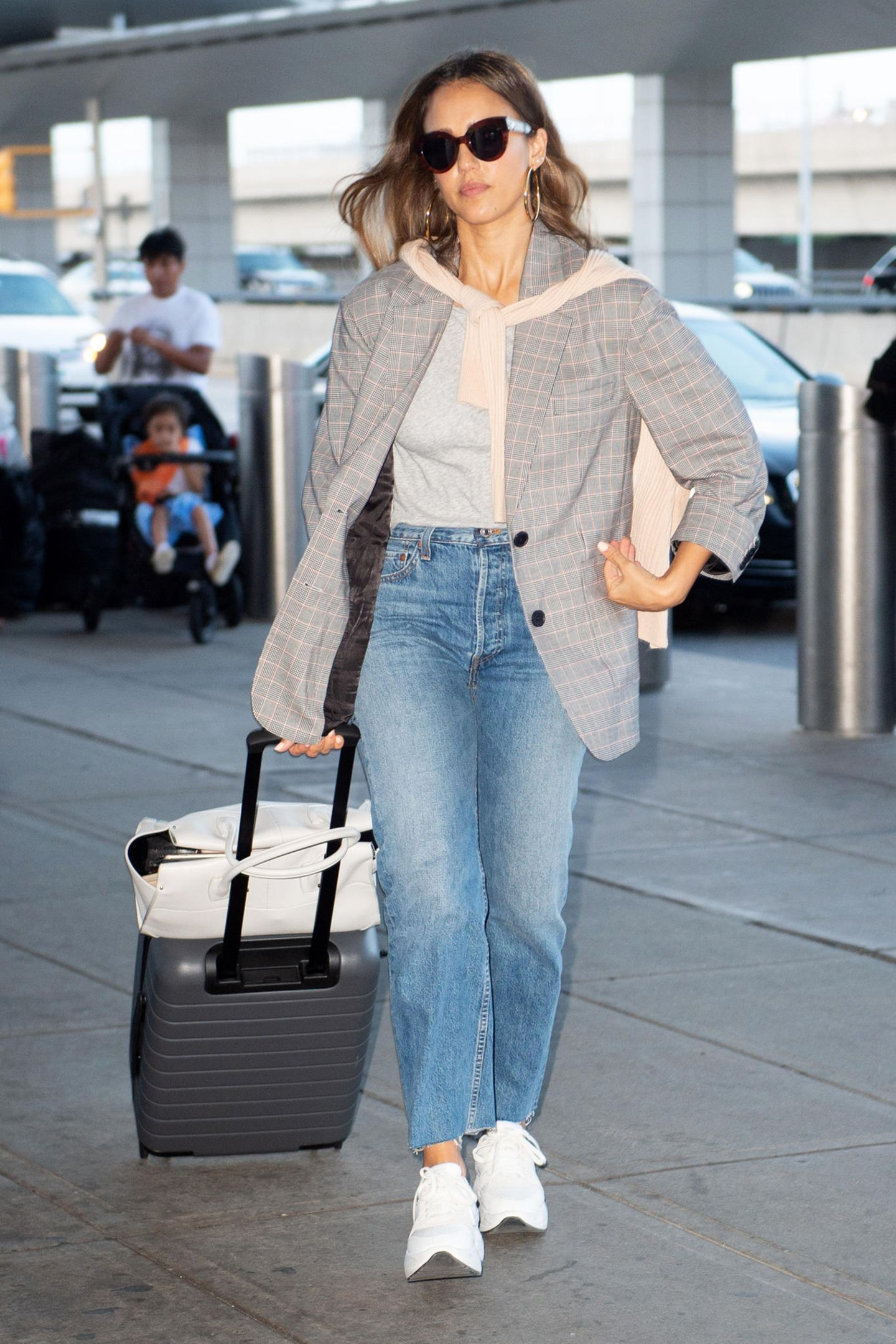 Für ihren Flug setzt Jessica Alba auf ein gemütlicheres Outfit: Ihr weißes T-Shirt hat sie gegen ein graues Modell gewechselt, ihre Jeans zu einer Variante mit ausgefranstem Saum und ihre Plateau-Sandalen hat die Schauspieleringegen weiße Sneaker ausgetauscht.