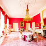 Einer der Räume des SchlossesNoordeinde ist einem farbenfrohen Rot gestrichen. Goldene Details wie der glamouröse Kronleuchter veredeln den Raum optisch.