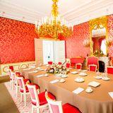 Ein Speisesaal mit roten Tapeten und goldenem Kronleuchter und Spiegel.