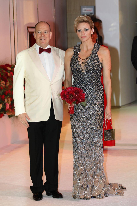 Zu Ehren des 70.Rot-Kreuz-Balls hüllt sich Fürstin Charlène in diese atemberaubende Robe von Atelier Versace und ist damit der Blickfang des Abends! Das Kleidmit seinem schönen Farbverlauf vonBlau zu Golderinnert dank seinesschuppenartigen Designs an die Flossen einer Meerjungfrau.