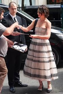 Beim Autogramme geben fällt besonders auf, dass Katie Holmes bei ihrem Designer-Kleid von Dior nicht ganz die richtige Größe ausgesucht hat.