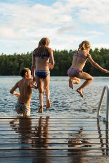 Kinder springen in einen Badesee.